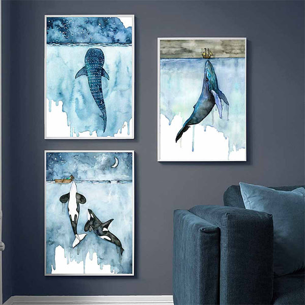Trio of whale canvas prints on blue wall