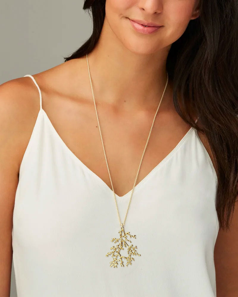 Model wearing a Coral Pendant on a long gold chain necklace