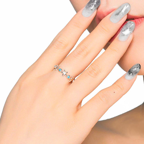 Woman wearing silver starfish ring on middle finger