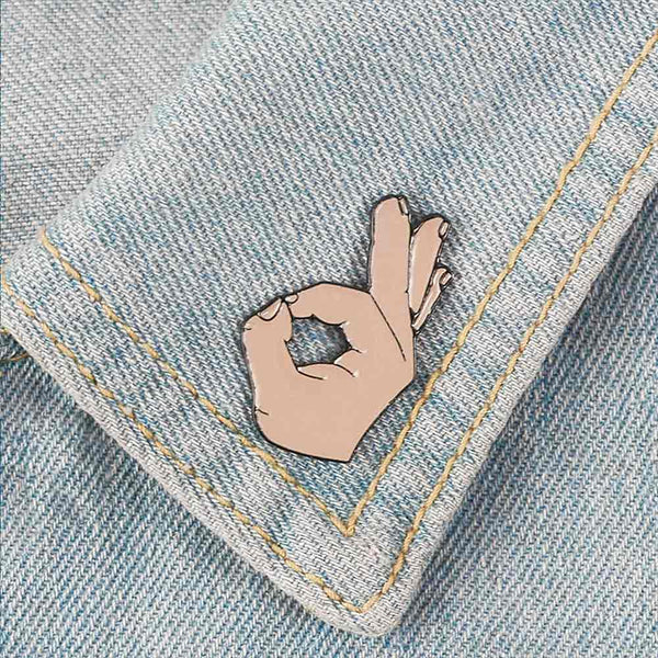 'OK' gesture pin on denim collar
