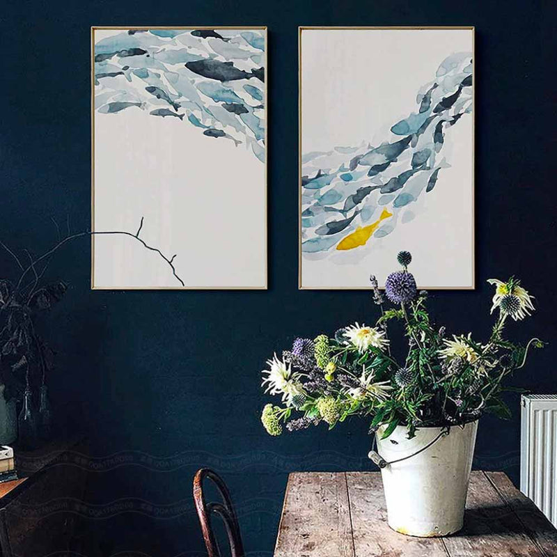 Two fish shoal canvases on a dark blue wall