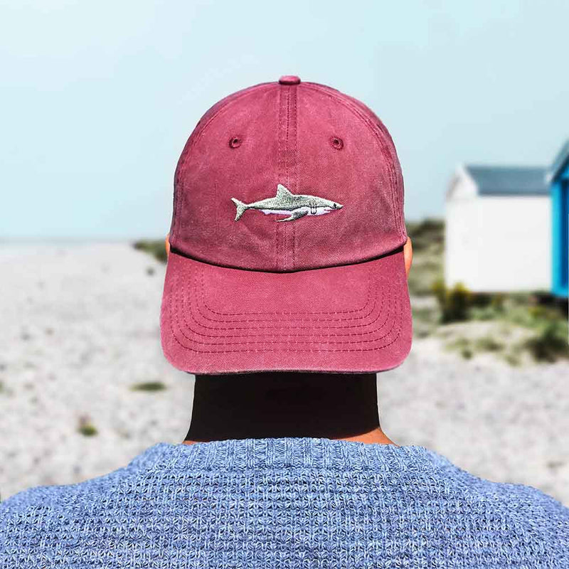 Man wearing back to front red baseball cap with shark design