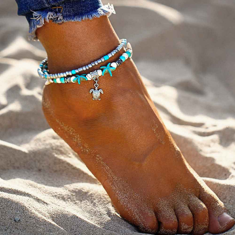 Woman wearing a Starfish Anklet with Turtle Charm on the beach