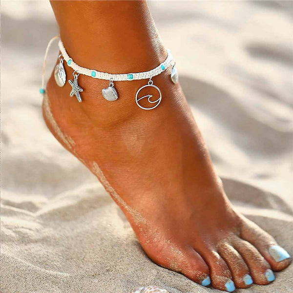 Woman wearing a woven anklet with shell and wave charms