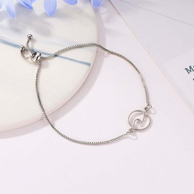 Wave charm bracelet in silver flat lay