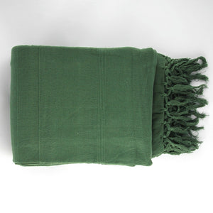 Woven cotton double bedspread with a textured weave and fringed edges in a deep forest green