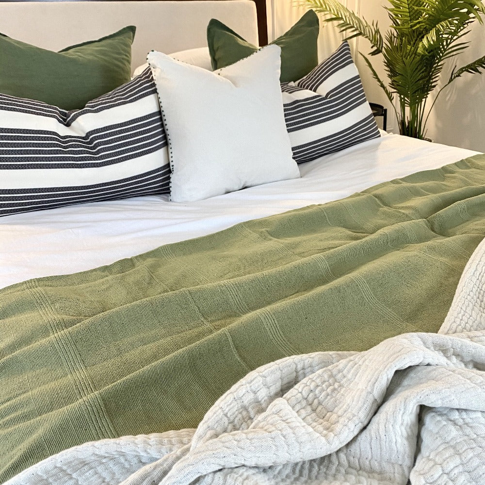 sage green bedspread on bed with green, striped and white cushions and a cream throw