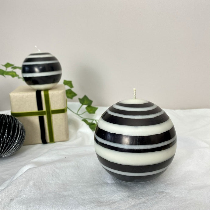 black and white striped ball candle with small candle, wrapped parcel and black and silver tree decoration in the background
