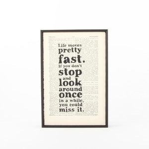 "Print featuring the quote ""Life moves pretty fast. If you don't stop and look around once in a while, you could miss it."" from movie Ferris Bueller. The quote is printed on a book page and has a slim black frame."
