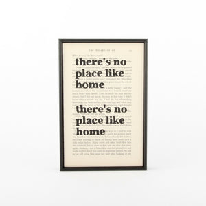 "Print featuring the quote ""There's no place like home. There's no place like home."" from the Wizard of Oz. The quote is printed on a book page and has a slim black frame."