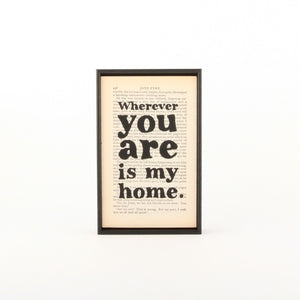 """Wherever you are is my home."" Charlotte Bronte quote printed on a book page from the novel Jane Eyre with a thin black frame"