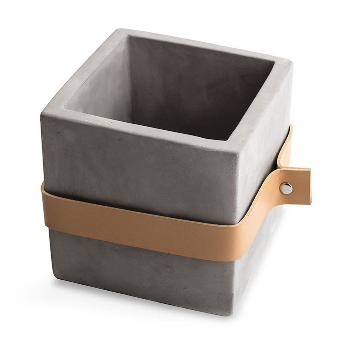 Square concrete planter with tan leather strap around the middle.
