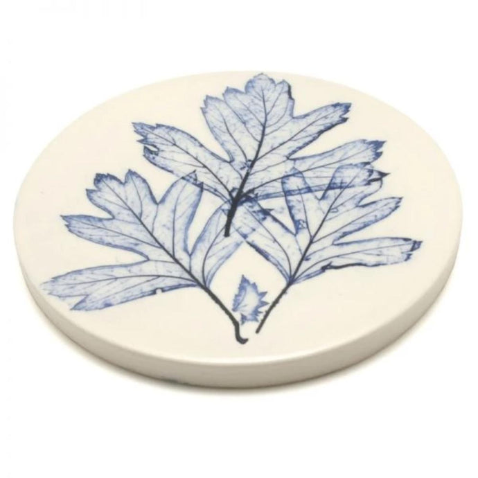 Handmade coaster made from clay with a leaf imprint in blue
