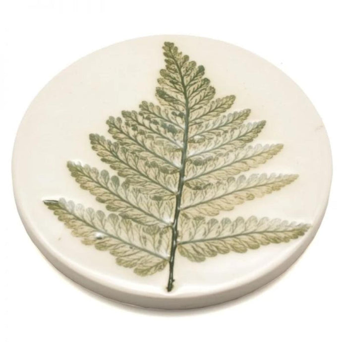 Handmade coaster made from clay with pressed leaf design painted in green