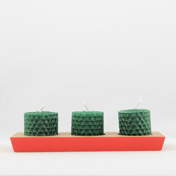 Wooden painted tealight holder painted red with three short green beeswax candles