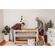 Gay couple in nursery with best crib mattress and changing pad