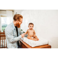 Dad and baby using white pebble changing pad