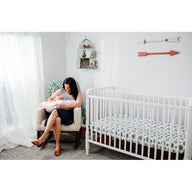 mom nursing baby with nursing pillow next to crib with best breathable baby crib mattress