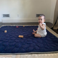 Baby sitting up on Navy Blue Nook Lilypad2 Best Baby and Toddler Play mat