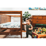 baby boy next to crib with best breathable baby crib mattress