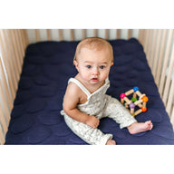 baby sitting on best breathable baby crib mattress