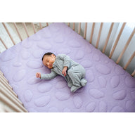 sleeping baby on safe sustainable cotton breathable crib mattress for baby and toddler purple lilac organic crib sheets