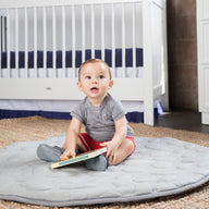 Baby boy reading book on grey LilyPad play mat - best play mat for baby