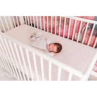 sleeping baby on safe sustainable cotton breathable crib mattress for baby and toddler pink organic crib sheets