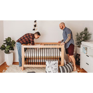 gay couple putting baby down on sustainable cotton breathable crib mattress for baby and toddler white