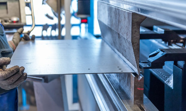 worker bending stainless steel with machine