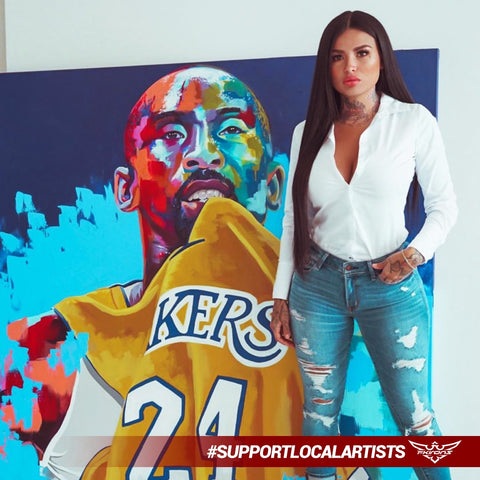 "Artist and model, known as ""Tatu Baby"" standing in front of her mural painting of Kobe Bryant"