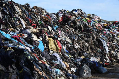 a mountain of discarded clothing in a landfill