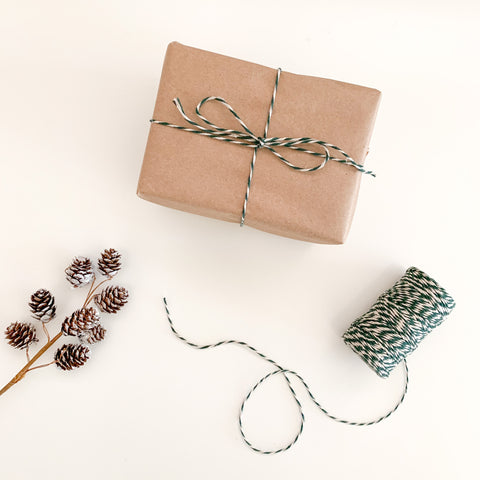 small rectangular brown kraft paper package tied with green and white flax twine.
