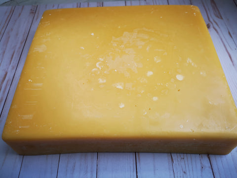 large, square beeswax slab sitting on a table, beeswax is one of the key ingredients in SOS skin repair balm