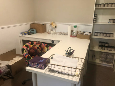 workspace at Twenty20 skincare featuring a super organized, white, L shaped desk and a bookshelf full of body butter jars, there are packing supplies behind the desk and a graphic, geometric print office chair.