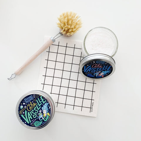 a white sponge cloth with a grid pattern surrounded by 2 mason jars with dish soap, and a wood, long handled dish brush