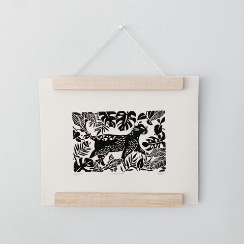 a lino cut print of a jungle cat hanging on magnetic, maple wood hangers on a light coloured wall