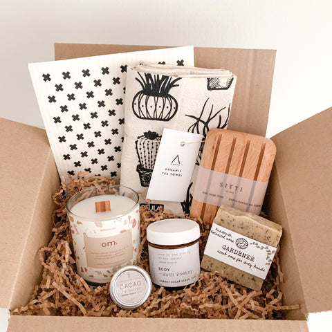 a gift box filled with Canadian products including a tea towel, sponge cloths, soap dish, soap, a candle, lip butter and a sugar scrub.