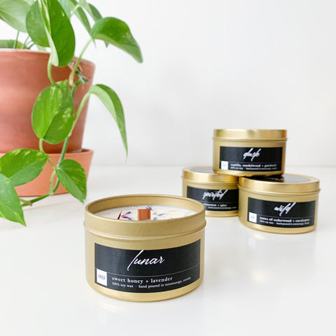 4 gold tin candles with black labels sitting on a white table beside a pothos plant. The candles have wood wicks and are sprinkled with some flower petals.