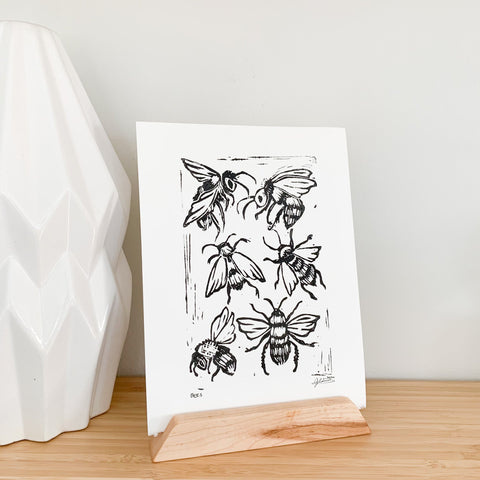 black, block print of bees on white paper sitting in a postcard holder, the print is sitting on a shelf beside a white planter
