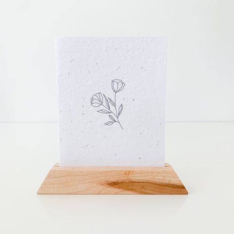 a seed paper card with a minimal line drawing of a flower on it, the card is sitting in a maple wood postcard holder