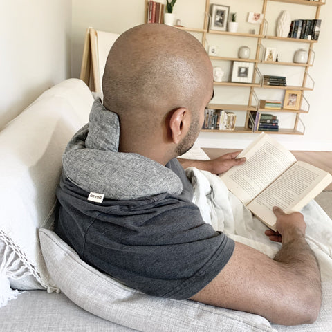 man sitting on a sofa reading with a neck bean bag draped across his shoulders and back of neck