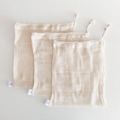 a set of three natural cotton coloured mesh produce bags laying on a white table