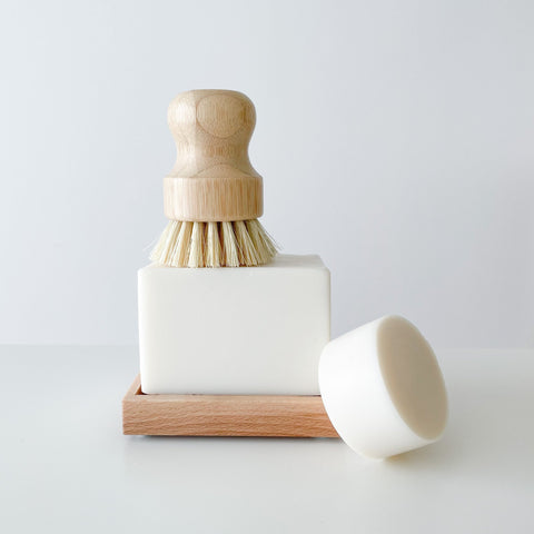 two white bars of soap. one is on a wood soap dish and the other which is smaller, is laying up against the bigger bar. there's a wood dish scrubbing brush sitting on top of the bigger bar.