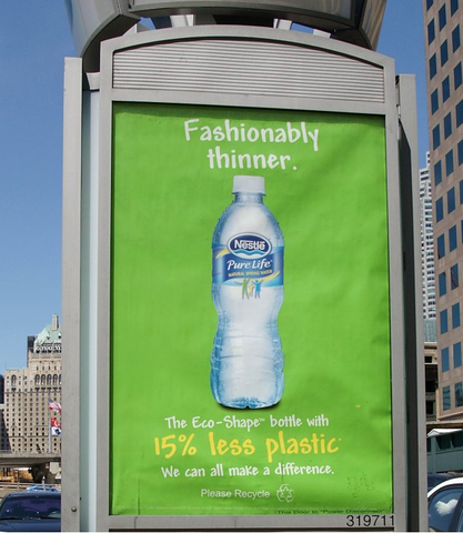 a poster of a nestle water bottle on a bus stop. The poster claims that the plastic bottle is made with less plastic.