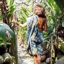 Load image into Gallery viewer, Young woman walking a path surrounded by spouted coconuts with her recycled travel beach towel by The Summer Chaser