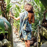 Young woman walking a path surrounded by spouted coconuts with her recycled travel beach towel by The Summer Chaser
