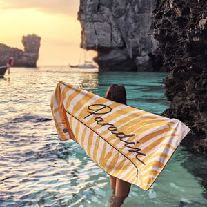 Young woman on the beach watching sunset in Phuket with her recycled travel beach towel by The Summer Chaser