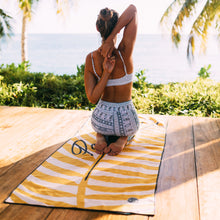 Load image into Gallery viewer, Young woman practicing yoga in front of the beach. Kneeling on Paradise towel by The Summer Chaser.
