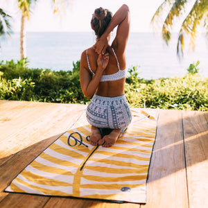 Young woman practicing yoga in front of the beach. Kneeling on Paradise towel by The Summer Chaser.